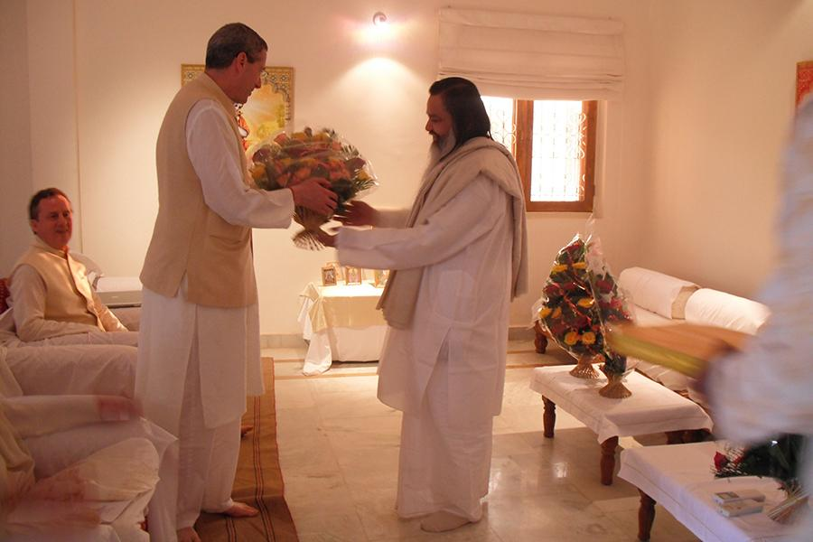 Brahmachari Girish Ji is offering flowers to Dr. Harris Kaplan at